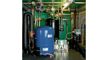 Air conditioning systems with heat recovery unit and reversible heat pumps