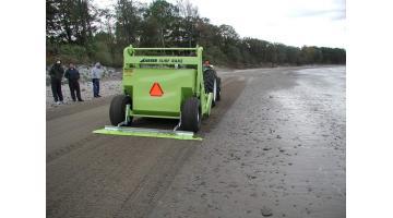 Macchina pulispiaggia trainata per spiaggia bagnata
